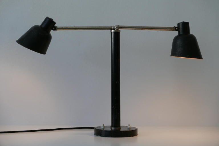 Spectacular double head Bauhaus modernist table lamp with adjustable arms and shades. Designed and manufactured in 1920s-1930s, Germany.