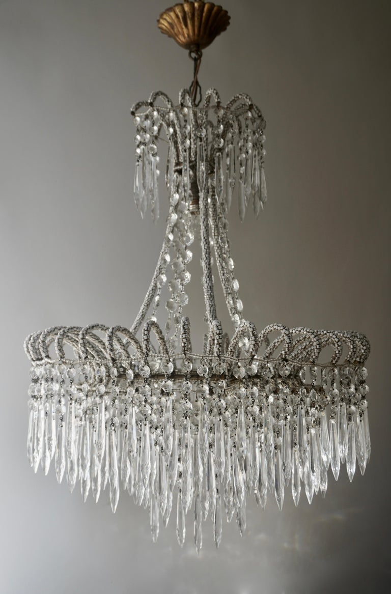 A crystal Victorian style waterfall chandelier with a brass frame that is covered with thousands of small polished white stones and three concentric rings hung with crystal icicle drops.  The light requires three single E14 and one E27 screw fit