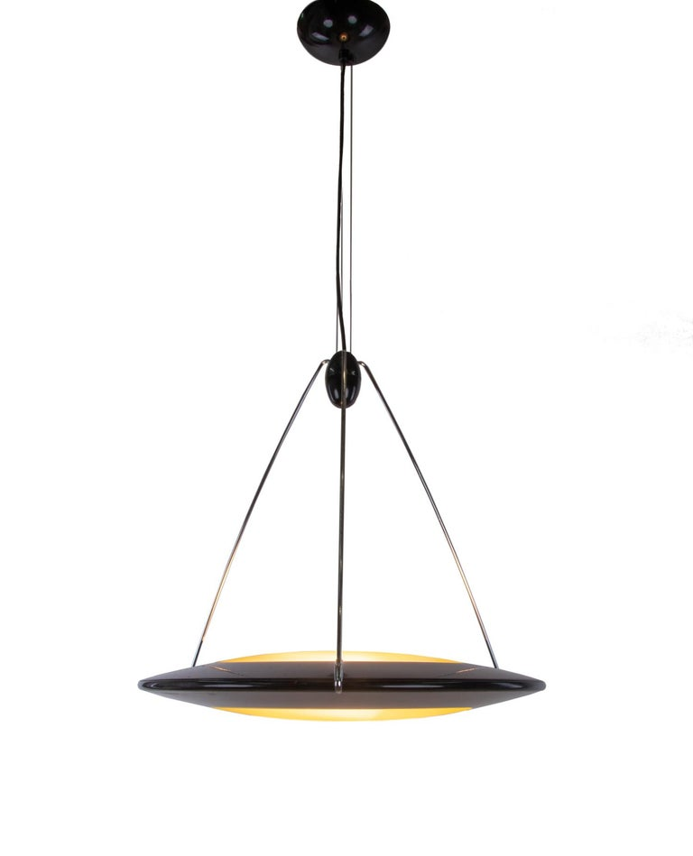 Postmodern UFO or flying saucer pendant light giving diffused upward and downward light. Designed in the 1990s by Ezio Didone and manufactured by Arteluce (in those years division of FLOS.), Milano, Italy.  A real eye-catcher even unlit. Gem from