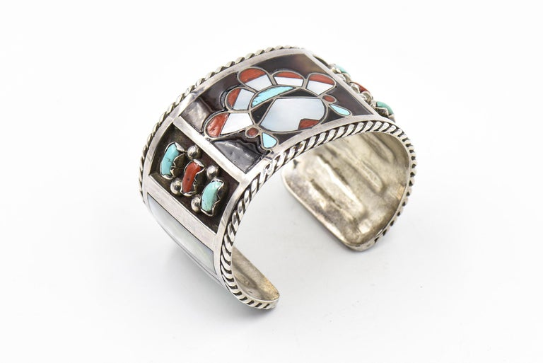 This beautiful bracelet is by Zuni artists Filbert & Clara Gasper.  Circa 1960 - 1970.  The bracelet is sterling silver with inlay turquoise, mother of pearl and coral.  In the center is an inlaid face and on the sides there are additional bezel set