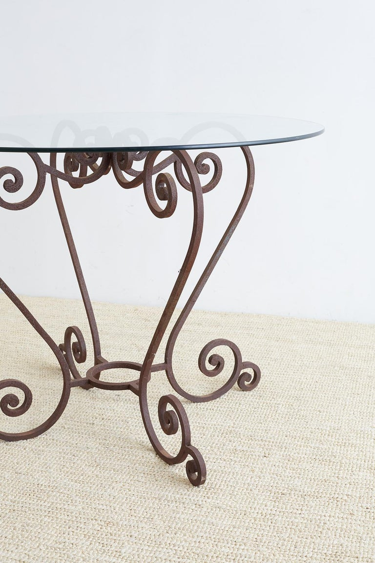 Elegant scrolled wrought iron breakfast table or patio garden table featuring four large S scrolls. Conjoined on top and bottom with scrolls on top and a ring stretcher on bottom. Each leg has a small scrolled foot. The table is constructed from