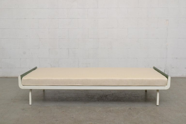Midcentury daybed designed for Auping in the Netherlands. Green stained wood ends with white enameled metal frame. Newly upholstered cushion in bone white fabric. Frame has visible wear consistent with its age and usage.