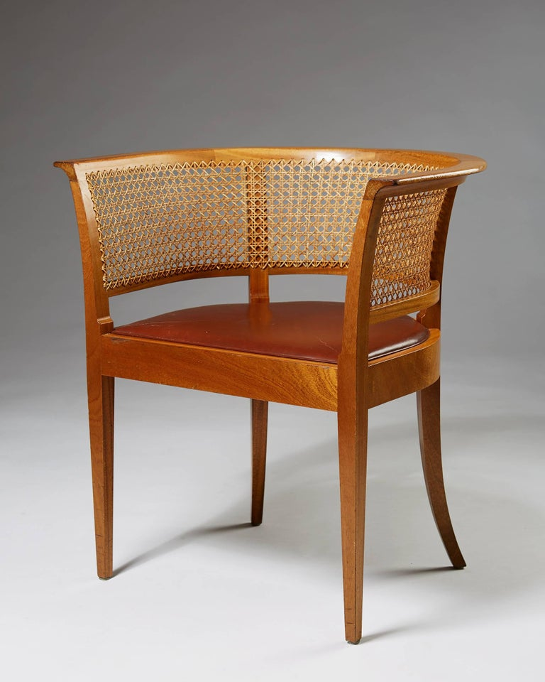 Mahogany, cane and leather.  This example made in the 1950s.  Measure: H 73 cm/ 2' 5 1/4'' W 70 cm/2' 4'' D 54,5 cm/ 21 1/2'' SH 45 cm/ 17 3/4''   In the history of Danish modernism, the Faaborg chair holds a special place. Designed by