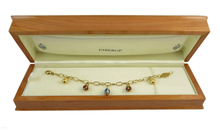 A delightful Easter egg bracelet by Faberge having five 18ct yellow gold egg charms evenly spaced along an 18ct yellow gold chain link bracelet.    The centre egg is decorated with a rich turquoise blue guilloche enamel into which are set four