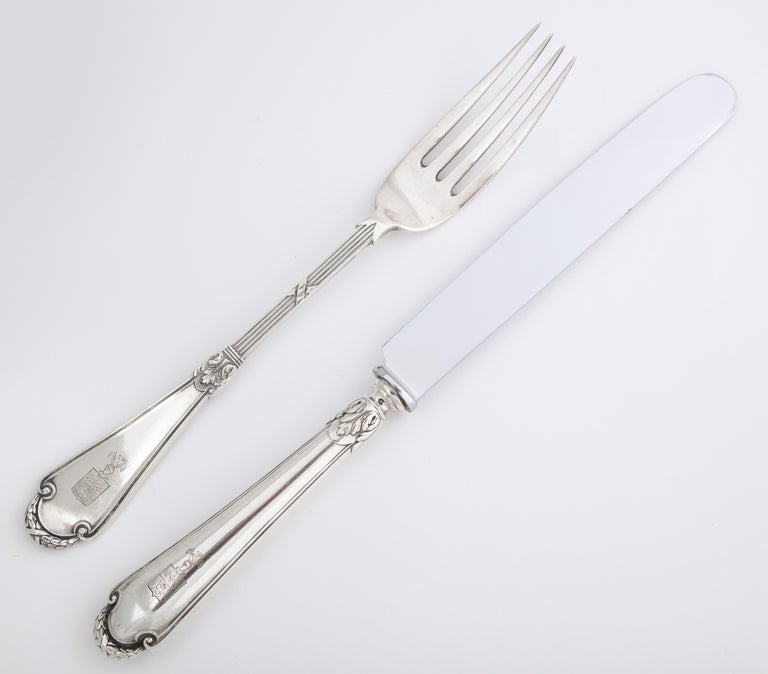 From the Romanov era, period of Czar Nicholas II, a silver knife and fork pair in the classical taste by Russia's most famous silversmith, Carl Fabergé, the fork enhanced with reed-and-tie stem and shaped handle, the knife en suite, fitted with a