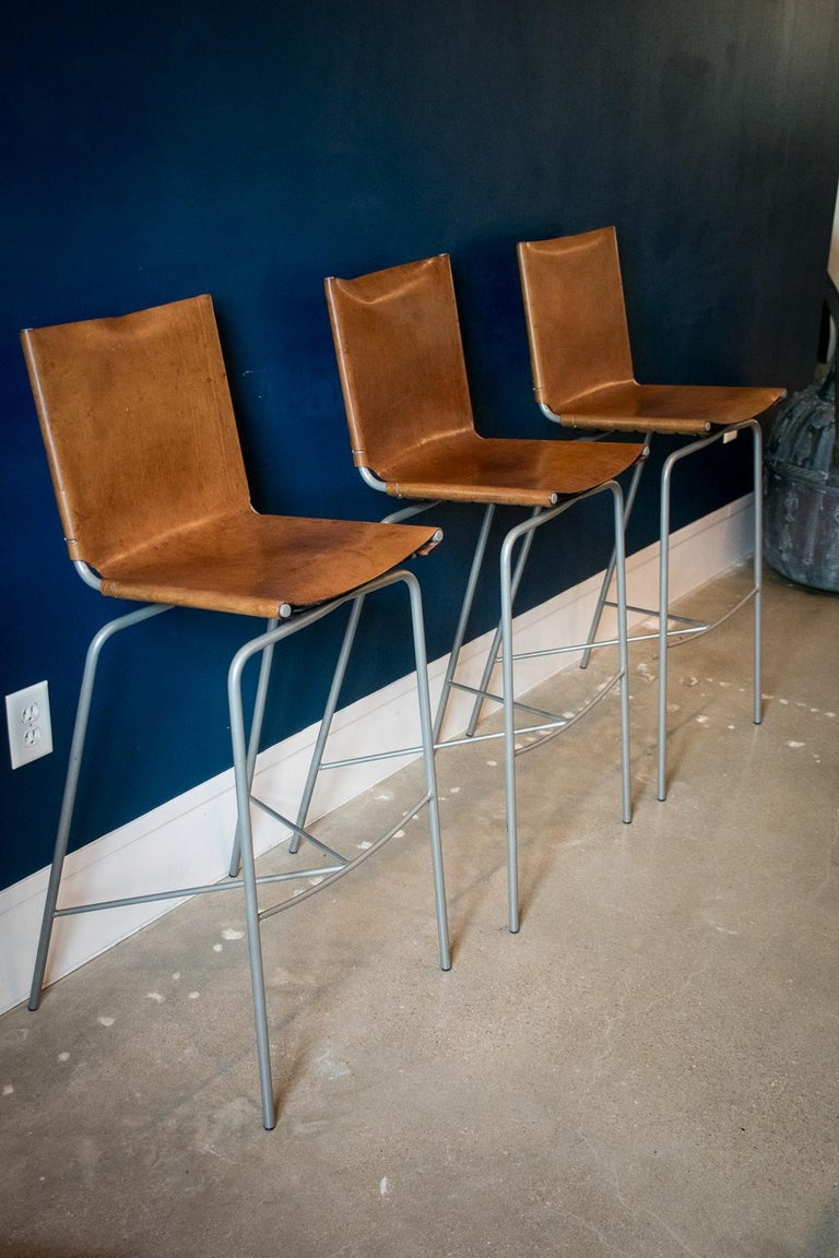 Crossed leg barstool, by Fabiaan Van Severan. Tubular steel frame, powder-coated gray with the crossed leg configuration, topped with heavy leather seats and tied in the back. Set of 3, Belgium, 1980s.