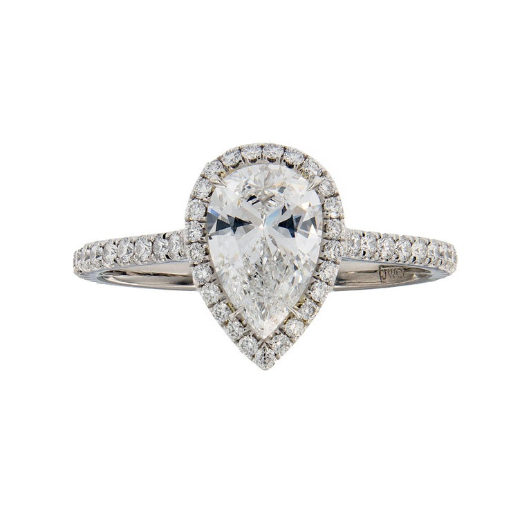 Stunning engagement ring hand fabricated in platinum. Ring centered around a 0.88 Carat D color, VS1 clarity pear shaped diamond embraced by a dazzling halo of french pave set diamonds. The diamond encrusted band gently curves up to meet the center