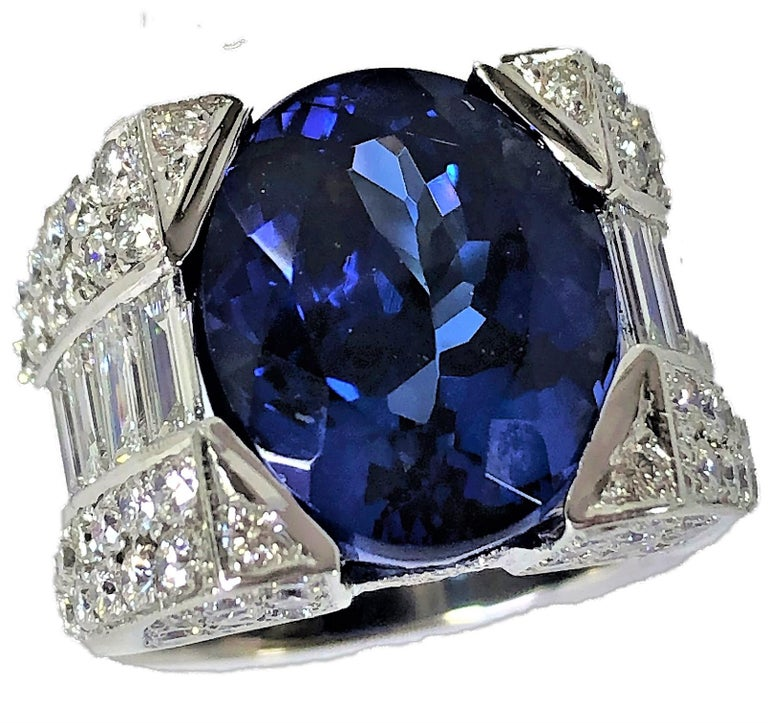 Set into a modern 18K White Gold mounting, this fabulous 12.06CT Tanzanite is truly brilliant AND.. it is the color of the deep blue sea. The mounting is set with assorted baguette and round brilliant cut diamonds weighing an approximate total of