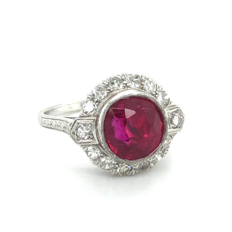 This charming Art Deco ring in platinum 950 features a stunning Burmese ruby. The cushion-shaped, untreated ruby weighs 4.41 carats and shows a beautiful red of incredible luminosity. The delicate and elegant mounting in platinum is set with 14