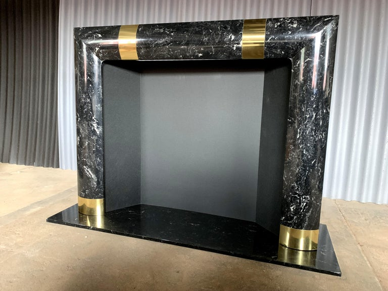 Beautiful and incredible fireplace surround with brass trimmings. This fireplace surround sits on a marble platform. Although quite heavy and substantial, I cannot confirm that it's real marble but a composite material. And once again, very heavy