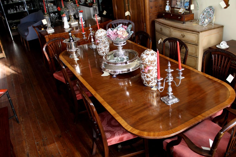 Magnificent old English Sheraton style figured mahogany dining table with very rare burr walnut crossbanding (inlay) on quad reeded pedestal with cast brass feet and casters. Measures: 72