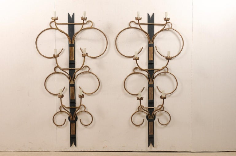 A fabulous pair of large-sized French Art Deco style sconces from the mid-20th century. These black and gold mid-century pair of sconces from France are impressively sized and just under 6 feet in height, and approximately 3 feet wide across their