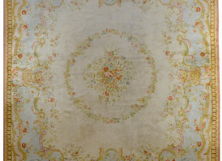 A fabulous vintage French Savonnerie rug with a traditional Baroque floral and scrolling S-curves woven in pale pinks, blues, greens, and gold's, against a pale blue background. The border is beautiful with a stylized architectural molding detail.