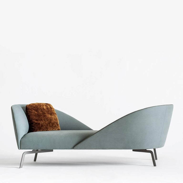 This superb sofa is a magnificent piece of functional decor that reinterprets lounging, transforming the living room into a space of interaction. The two mirroring backrests of this elegant object of functional decor are accessorized with