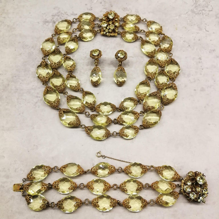 A very sumptuous and very glamorous parure, necklace, bracelet and earrings, from Miriam Haskell in the 1960s. Composed of faceted faux citrine ovals, held in gilt metal terminals, the clasp of both the necklace and the bracelet have typical Haskell