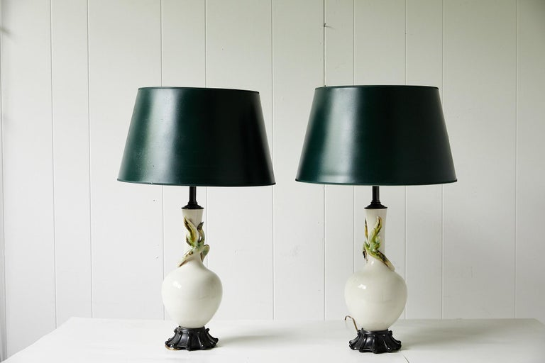 Early 20th century facing pair of lamps made of cream ceramic and in a simple vase form. Each lamp has a slightly different ceramic bird of green and brown tones decorating it's neck. The lamps are mounted on carved wooden bases and topped with