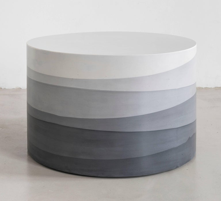 An exploration in the softness and subtly of the materials, the made-to-order coffee table has a hollow cavity and is cast entirely from hand-dyed cement. Poured in individual hand-dyed layers, starting from the base color black and fading to white,