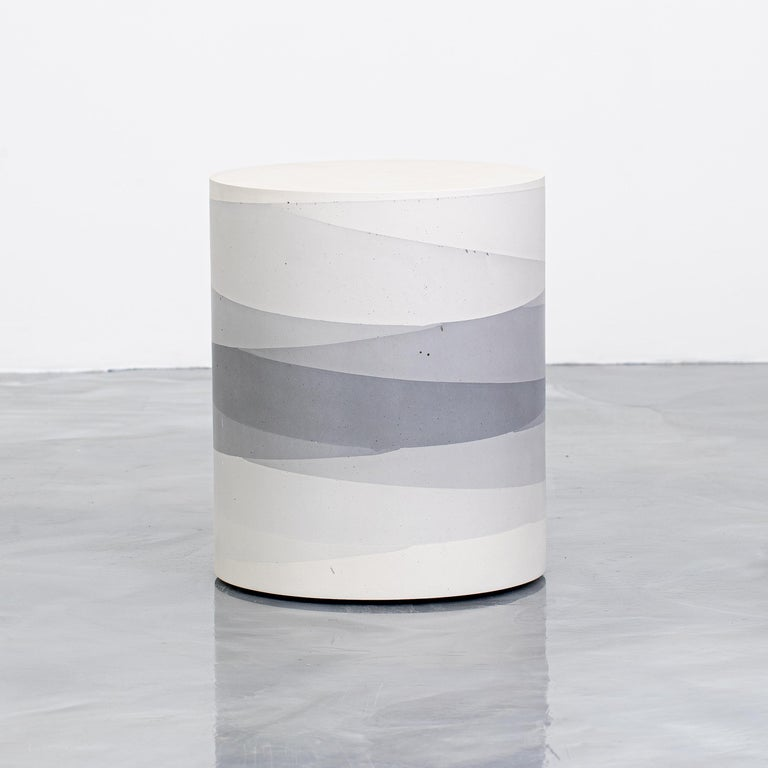 An exploration in the softness and subtly of the materials, the made-to-order drum has a hollow cavity and is cast entirely from hand-dyed cement. Poured in individual hand-dyed layers, starting from the base color grey and fading to white, the