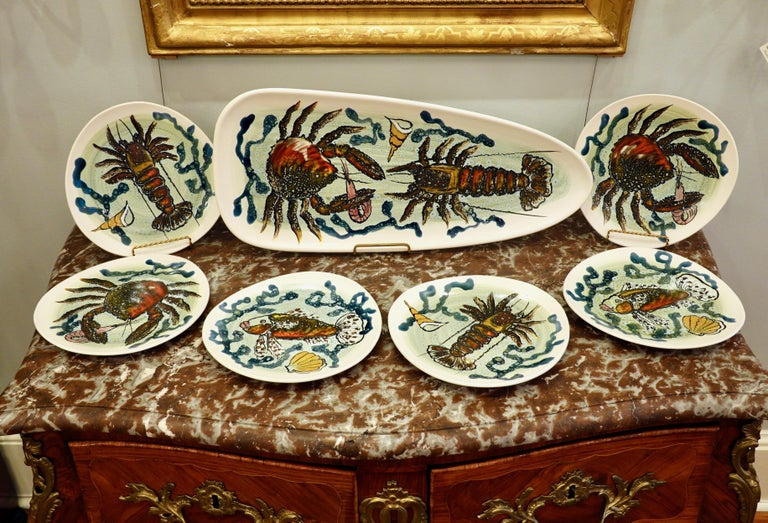 14 piece highly-decorative French hand painted faience fish service, featuring lobsters, crabs, fish and other sea life. The service consists of a platter (about 24