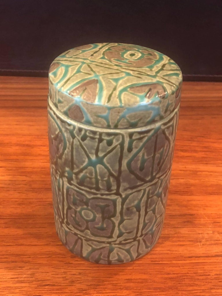 Fajance ceramic lidded jar / humidor from the Baca line by Nils Thorsson for Royal Copenhagen, circa 1960s. The green glazed stoneware jar with geometric abstract design in relief was designed by Royal Copenhagen's renowned artistic director, Nils