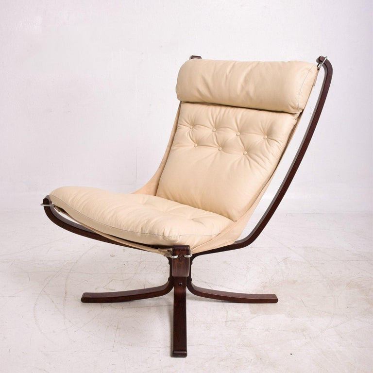 For your consideration a vintage Falcon lounge chair by Wetnofa. Norway circa 1960s. Bentwood legs in sculptural shape in dark rosewood stain. (Original). Canvas has aged sun fade. New leather cushion in ivory color.   Measures: 38 3/8