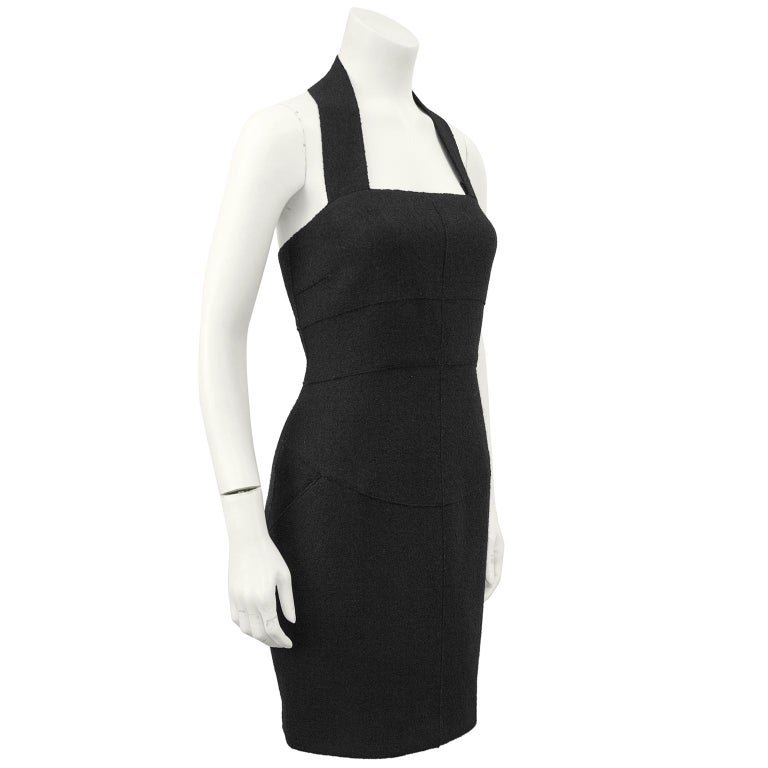 1999 Fall Chanel black wool halter dress with two hip front pockets and seaming down the front. The dress zips up the back and the thick halter strap fastens at the nape of the neck with a black CHANEL button. In excellent condition, fully lined in