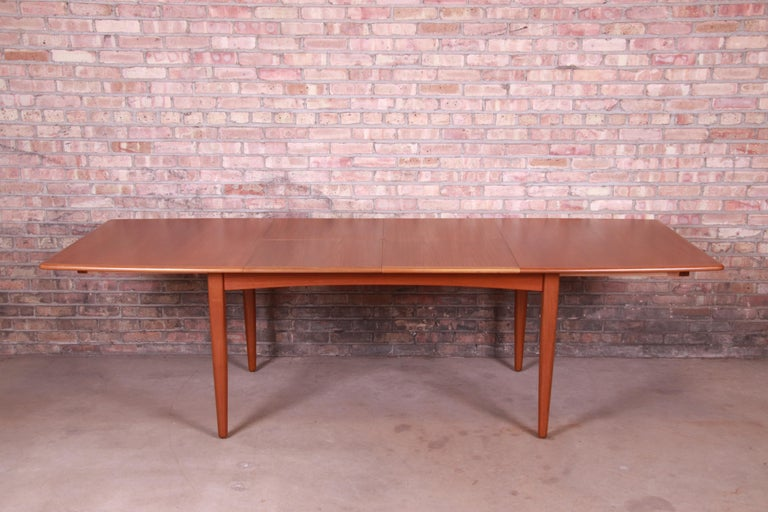 An exceptional Danish modern teak boat-shaped extension dining table