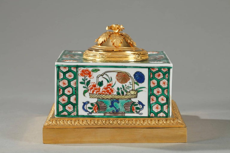 Small famille verte ?porcelain?inkwell decorated with enameled flowerpots, foliage, and stylized rinceaux. The inkwell is set on a gilt bronze base that is decorated with palmette and bands embellished with interspaced latticework encircle the