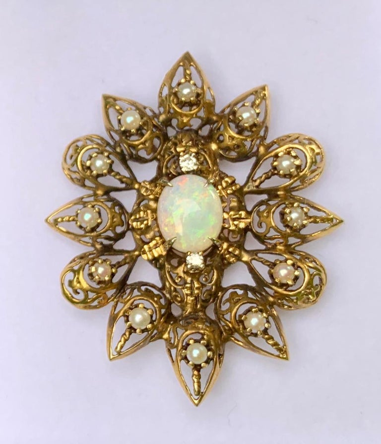 Exquisite, antique estate, late Victorian, hand made fanciful filagree openwork opal, diamond and pearl brooch pendant is an elaborately detailed oval starburst-type shape and is constructed out of 14 karat yellow gold which has a natural antique