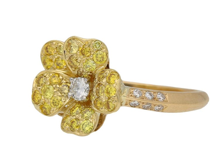 Fancy colour diamond flower ring by Oscar Heyman Bros. Set with thirty one round brilliant cut natural unenhanced yellow diamonds in open back grain settings with a combined approximate weight of 0.27 carats and further enhanced by thirteen round