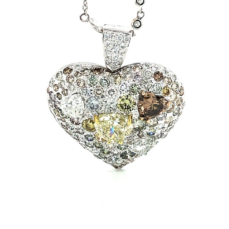 Offered here is a unique 18kt white gold heart shape pendant set with fancy shape and fancy color diamonds. Truly a one of a kind piece. The pendant has four ( 4 ) heart shaped diamonds. One natural yellow diamond Si1 in clarity and weighs 3.00