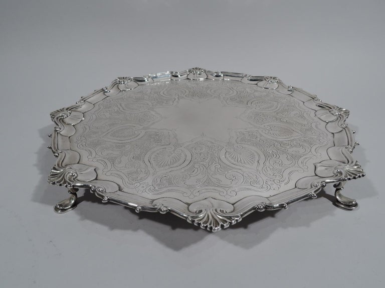 Victorian Georgian sterling silver salver. Made by William Hutton & Sons, Ltd in Sheffield in 1898. Round shaped well, engraved with dense ornament: Palmettes surrounded by scrollwork and flowers. Center has star cartouche (vacant). Molded