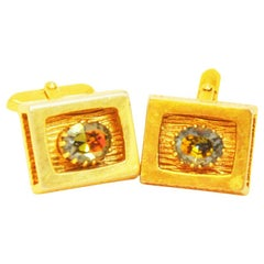 Fancy goldcoloured cufflinks of the sixties with colorful rhinestones