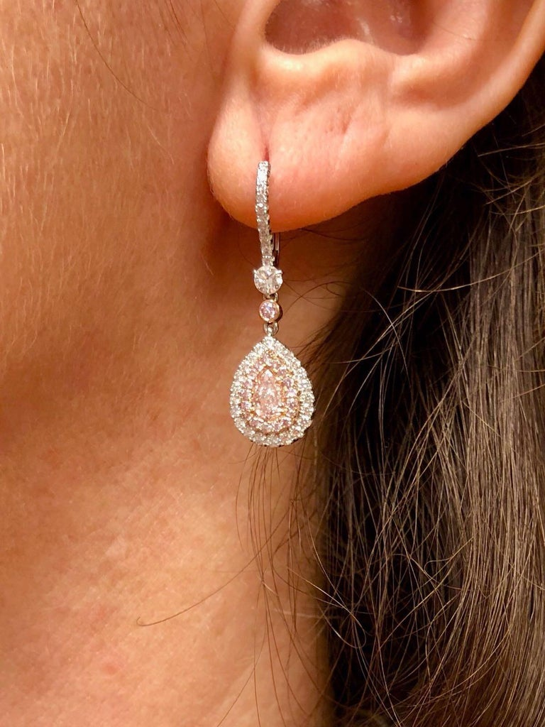 Pink Diamond earrings for women, unveiling a romantic pair of Fancy Light Pink diamond pear shapes (0.26ct and 0.27ct), weighing a total of 0.53ct, surrounded by a total of 0.28ct fancy pink round brilliant diamonds, and 0.49ct total F color and VS
