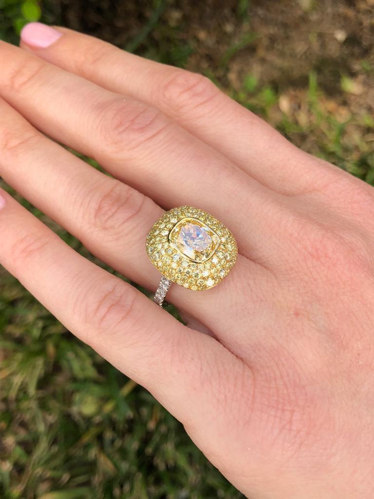 Notable 3.01 carat cushion cut, Fancy Light Yellow diamond, VS1 clarity,  surrounded by an array of 1.41 carat total round brilliant Fancy Yellow Diamonds, and accented by a total of 0.41 carat round brilliant, F-G color, VS clarity diamonds, set