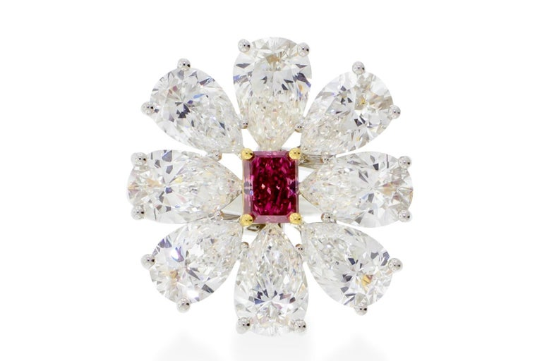 A 0.44 carat fancy vivid pink radiant cut center stone set in 18K yellow gold surrounded by 8 pear shapes diamonds weighing 6.12 carats set in platinum that come together to make a beautiful delicate flower. GIA certified. Report No. 1172177345.