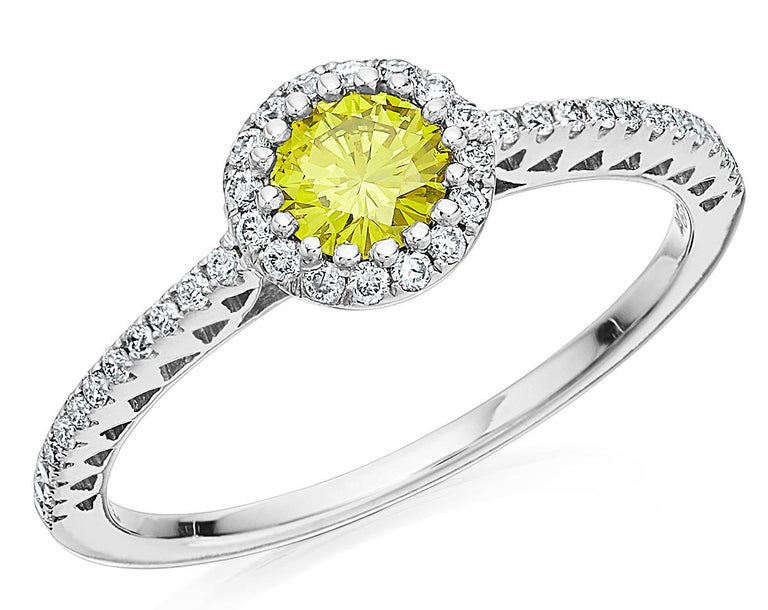 Yellow diamond and white diamond cluster ring consisting of a very slightly greenish yellow diamond as main eye-catcher, further surrounded with white diamond and completed with more diamonds on the shoulders. 1 X Fancy Vivid Yellow Diamond Round
