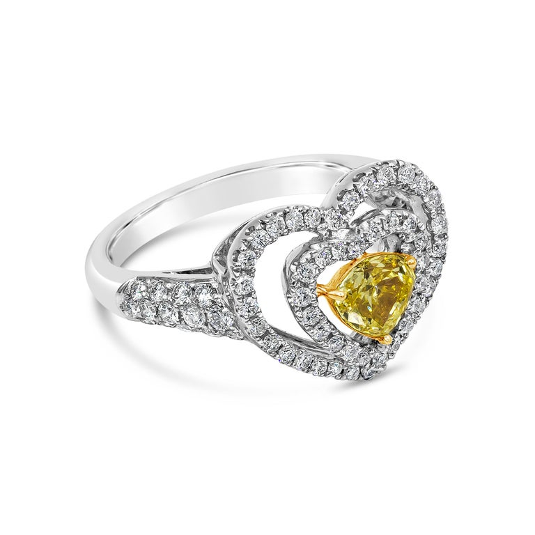 A unique and chic engagement ring showcasing a 0.58 carat yellow diamond, set in an open-work double halo design shaped like a heart. Accent diamonds weigh 0.72 carats total. Made in 18 karat white gold. Size 6.5 US (sizable upon request).  Style