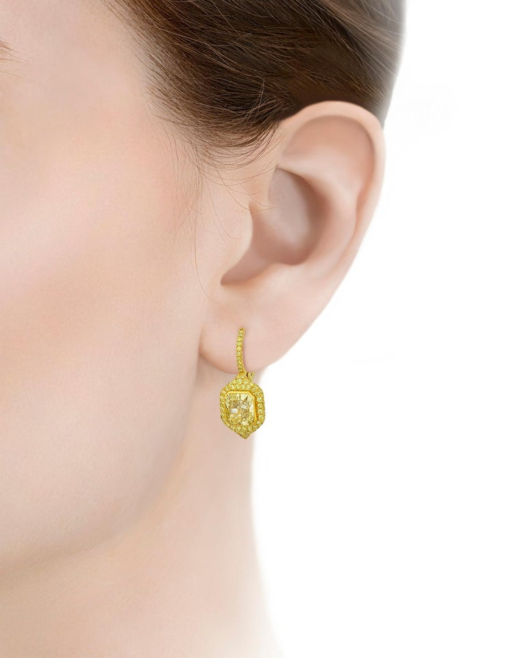 Two natural fancy yellow diamonds totaling 4.91 carats are set in these dazzling drop earrings. The duo, which weigh 2.48 carats and 2.43 carats, are certified by the Gemological Institute of America as entirely natural. The larger of the two