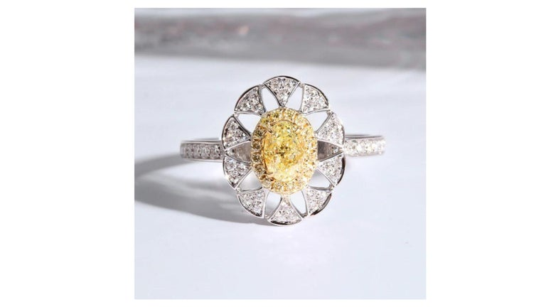 This Fancy Yellow diamond ring stands out with 37 diamonds set in 18 Karat White Gold.    Diamonds: Natural Diamonds  Mainyellowdiamond: 0.4ct  Assistant diamond:0.5ct  allCarat Weight: 0.9ct  Cut: Oval shape Clarity: SI Color: G-F