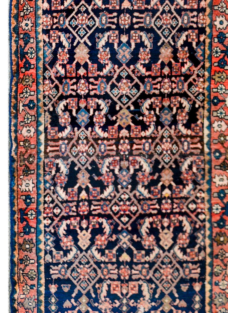 A fantastic early-20th century Persian Hamadan rug with an all-over mirrored trellis pattern of flowers and vines, woven in crimson, pink, light indigo, and white colored wool, on a dark indigo background. The border is complex with a large-scale
