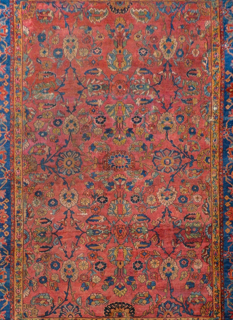 A fantastic early 20th century Persian Sarouk Mahal rug with an all-over field of flowers and vines woven in light and dark indigo, pale green, cranberry, and gold on a cranberry background surrounded by a wonderful border woven with large-scale