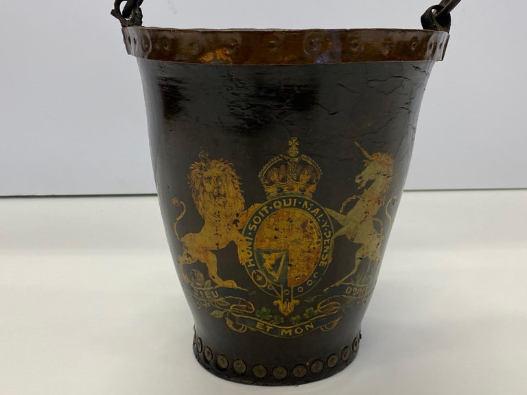 A fabulous character rich early English fire bucket, hand painted with regal crest of two horses and oval medallion with crown. Original leather handle.