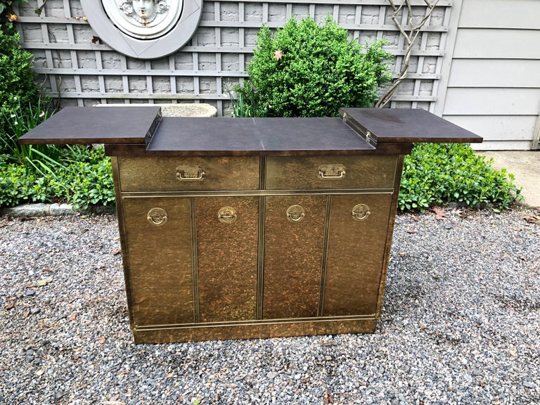 A rare midcentury brass clad bar and cabinet by Mastercraft. The bar features a lacquered faux wooden top that opens to a laminate surface suitable for serving drinks. The interior has two drawers and four shelves for storage. The bar has the iconic