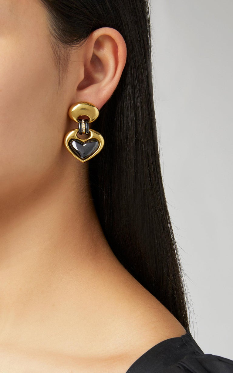 A chic heart-shaped 18K Yellow Gold and Hematite Ear-clips with Diamond Accents by Faraone. Made in Italy, circa 1970.