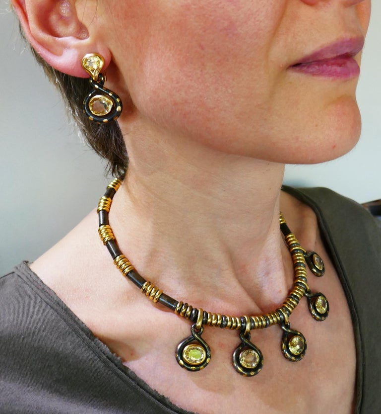 Fabulous set consisting of a necklace and a pair of earrings created by an Italian jewelry company Faraone. It is made of 18 karat yellow gold and gun metal and set with oval faceted yellow sapphires. Beautiful contrast of the shiny yellow gold and