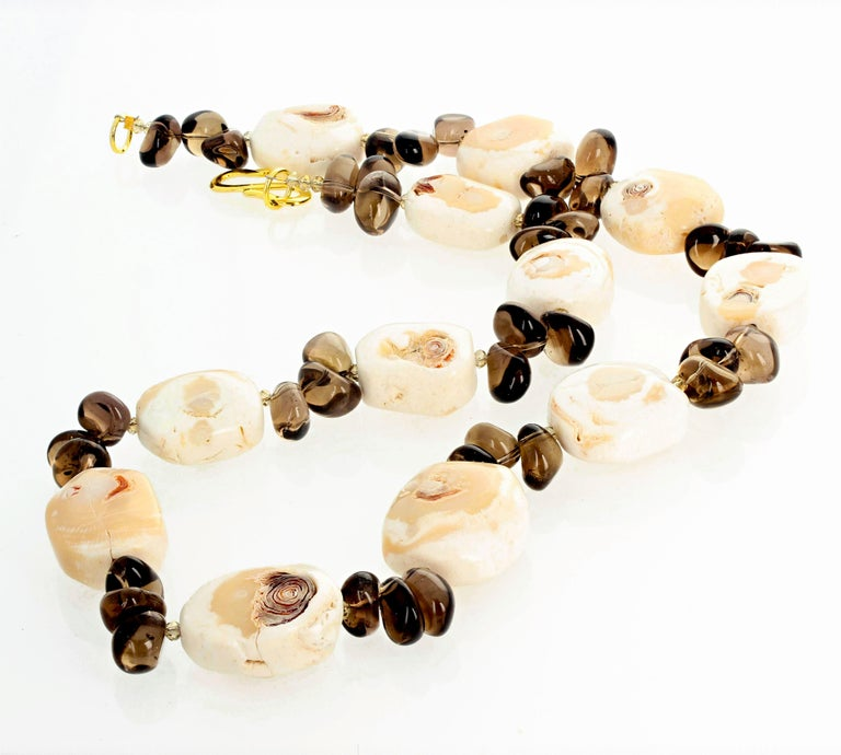 Roughly polished artistic natural Coral enhanced with briolets of natural Smoky Quartz swing beautifully in this lovely 24 inch long necklace with gold plated easy to use hook clasp.  This ready just in time for summer and we can shorten it for free