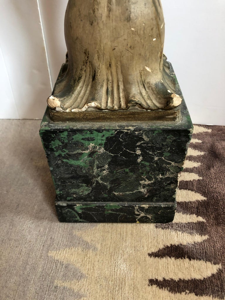 Two carved wood elongated tall architectural fragments that we call feather sculptures, mounted on faux painted green marble bases. The tops are flat so could support a console top.