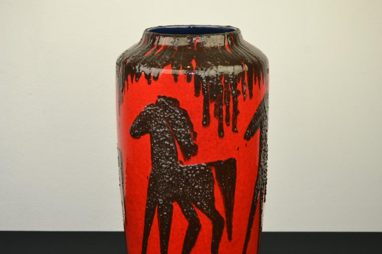 1960s Fat Lava vase with horses. This Western Germany Art Pottery Vase by Scheurich has the color red with dark brown, black horses on. The design is embossed or with relief on this vintage red vase. Inside the vase has the beautiful color
