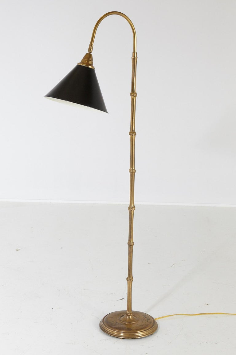 Faux bamboo brass floor lamp with swiveling black metal shade.  The brass is of heavy, excellent quality, a solid construction. Some tarnish to base, from age and consistent use, please refer to the photos. Measurements: Base diameter 10 x height